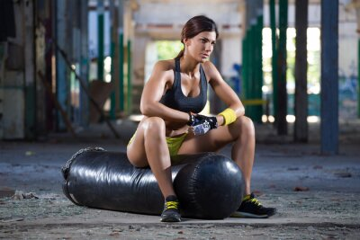 Bild girl seating on boxing bag