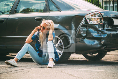 Bild girl sits on the road, near the broken car and calls on the phone, calling for help.