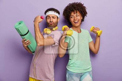 Bild Glad multiethnic husband and wife attend sport center, exercise with dumbbells, hold fitness mat, stand back to each other, have funny happy looks, wear t shirts, isolated on purple background
