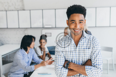 Bild Glad young man with african hairstyle posing with arms crossed in his office with other employees on background. Male manager in blue shirt smiling during conference at workplace.