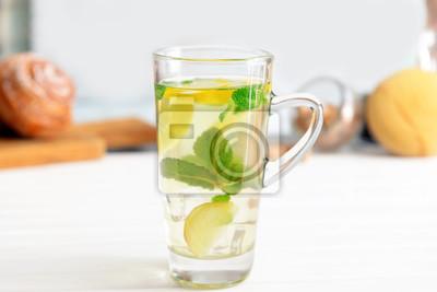 Bild Glasschale kalter Minztee mit Zitrone und Ingwer auf Tabelle