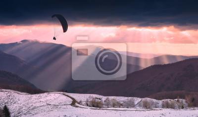 Gleitschirmschattenbild über den Strahlen des Sonnenunterganglichtes