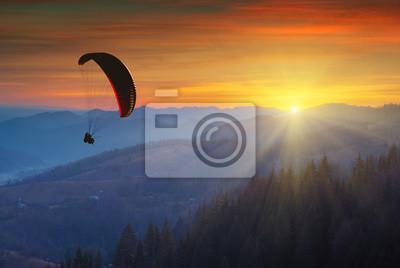Gleitschirmschattenbildfliegen in einem Licht des bunten Sonnenaufgangs