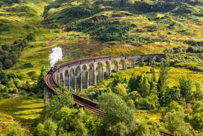 Bild Glenfinnan Railway Viaduct in Schottland mit dem Jacobite Dampfzug vorbei