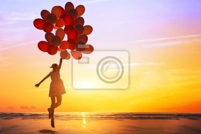 Bild Glück oder Traum Konzept, Silhouette der glückliche Frau springt mit bunten Luftballons bei Sonnenuntergang am Strand