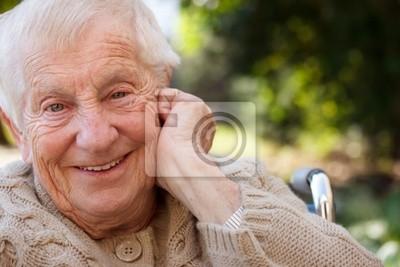 Glückliche ältere Dame im Rollstuhl lächelnd außerhalb