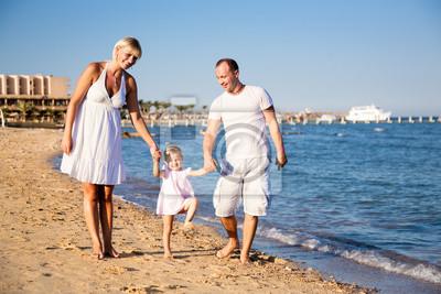 Glückliche Familie am Strand spielen