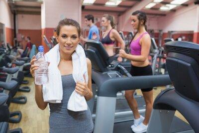 Glückliche Frau trinkt Wasser im Fitness-Studio