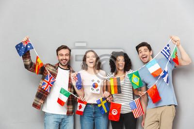Bild Glückliche Gruppe Freunde, die viele internationalen Flaggen halten.