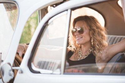 Bild Glückliche, sorglose Frau genießen ein Retro-Auto, heißer Sommertag.