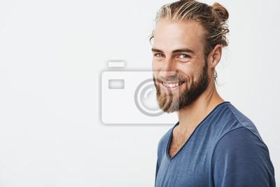 Bild Glücklicher junger bärtiger Kerl mit der modernen Frisur und Bart, der Kamera betrachtet, hell lächelt mit den Zähnen, glücklich über freien Tag auf Arbeit.