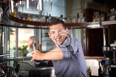 Bild Glücklicher lächelnder Barmixer, der ein Cocktail im Stahlrüttler rüttelt.