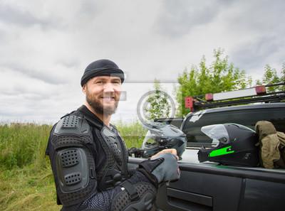 Bild Glücklicher lächelnder junger Mann, der draußen Motorradgang trägt und die Kamera betrachtet.