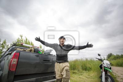 Bild Glücklicher lächelnder junger Mann mit den breiten Armen öffnen sich draußen tragenden Motorradgang und betrachten die Kamera.