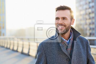 Bild Glücklicher Mann, der draußen während des sonnigen Wintertages steht