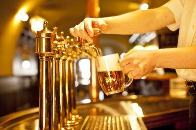 Bild gold beer in the hand and beer taps