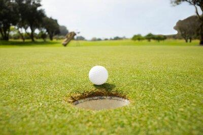 Bild Golf Ball auf dem Rand des Loches