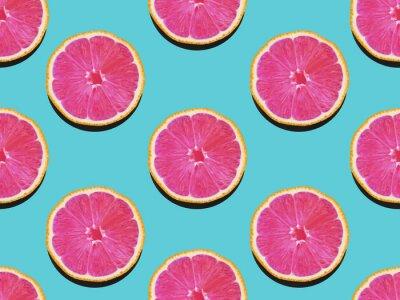 Bild Grapefruit im flachen lay Fruchtiges Muster der Grapefruit mit rosa Fleisch auf einem türkisfarbenen Hintergrund Draufsicht Modernes flach lay Foto Muster im Pop-Art-Stil