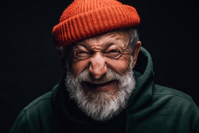 Bild Grey- haired aged grandfather feeling overjoyed and excited while telling about his trip to mountains. Old man dressed in red knitted hat and green hoodie. Happy to be active in retirement