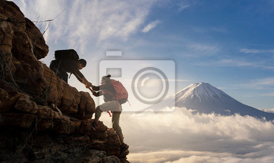 Bild Group of Asia hiking help each other silhouette in mountains with sunlight..