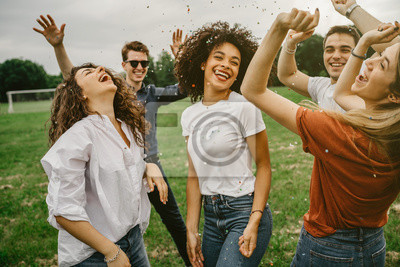 Bild Group of five friends having fun at the park - Millennials dancing in a meadow among confetti thrown in the air - Day of freedom and carefree