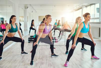 Gruppe von Frauen machen Kniebeugen in Fitness-Studio