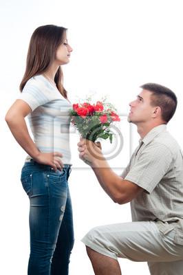 Gut aussehender junger Mann mit Rosenstrauß zu seiner Freundin