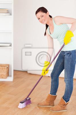 Gute lookingl rothaarige Frau fegt den Boden zu Hause