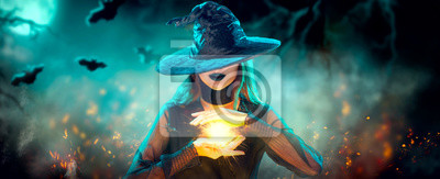 Bild Halloween Witch girl with making witchcraft, magic in her hands, spells. Beautiful young woman in witches hat conjuring. Spooky dark magic forest background. Magician. Wide Halloween party art design