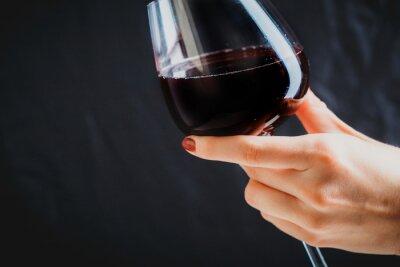Bild Hand hält Glas Rotwein auf dunkelgrauem Hintergrund