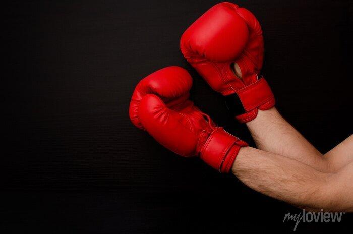 Bild Hand in roten Boxhandschuhen in der Ecke des Rahmens auf einem schwarzen Hintergrund, leeren Raum