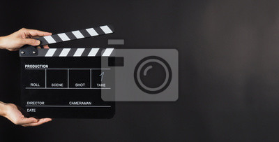 Bild Hand is holding Black clap board or movie slate  use in video production , movie ,film, cinema industry on black background.It have write in number.