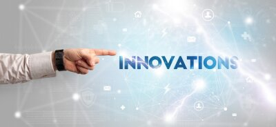 Hand pointing at INNOVATIONS inscription, modern technology concept