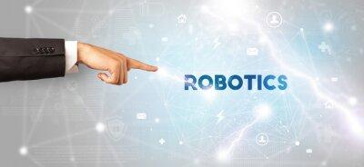 Hand pointing at ROBOTICS inscription, modern technology concept