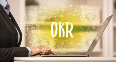 hand working on new modern computer with OKR abbreviation, modern technology concept