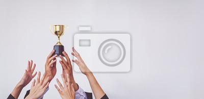 Bild Hands scramble for the golden trophy cup, concept business
