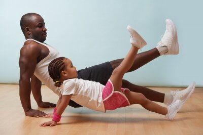 Bild Handsome black young father and his cute little daughter are doing reverce plank with leg raise on the floor at home. Family fitness workout.