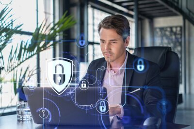 Bild Handsome businessman in suit at workplace working with laptop to defend customer cyber security. Concept of clients information protection and brainstorm. Padlock hologram over office background.