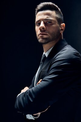 Bild Handsome confident man in black suit with arms crossed on dark background