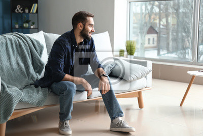 Bild Handsome fashionable man sitting on sofa at home