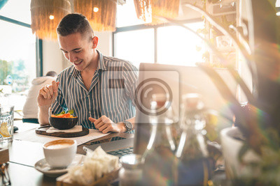 Bild Handsome man eating a salad while doing business. - Stock Image