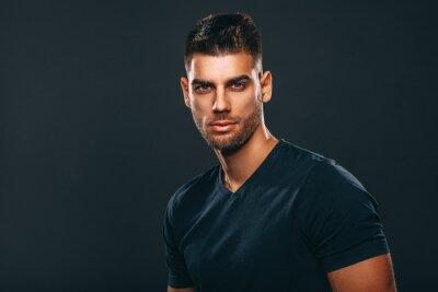 Bild Handsome man posing in studio on dark background