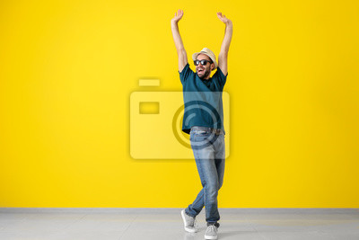 Bild Handsome young man dancing near color wall