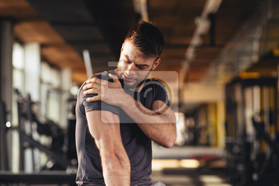 Bild Handsome young man feeling the pain in shoulder at the gym