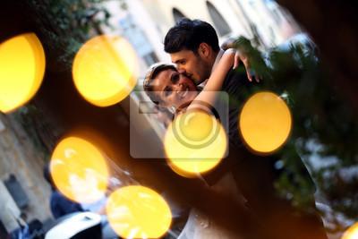 Bild Happy beautiful wedding couple posing in city