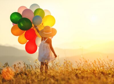 Bild . happy child with balloons at sunset in summer
