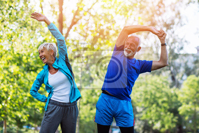 Bild Happy fit senior couple exercising in park.