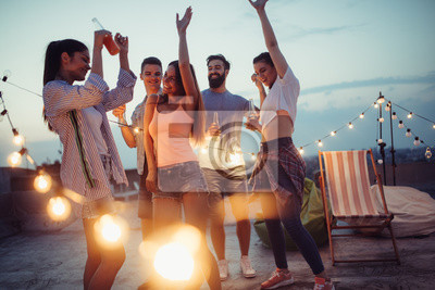 Bild Happy friends with drinks toasting at rooftop party at night