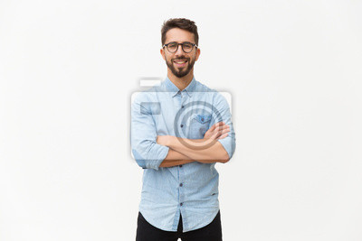 Bild Happy laughing guy posing with arms folded. Handsome young man in casual shirt and glasses standing isolated over white background. Male portrait concept