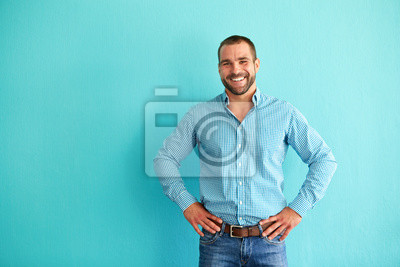 Bild Happy man in front of turquoise wall